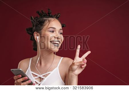 Image of cute punk girl with bizarre hairstyle and dark lipstick showing peace fingers while using smartphone with earphones isolated over red background poster