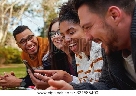 Group Of Multi Ethnic Friends In College Lying Together In The Park Enjoying Watching Text Or Video
