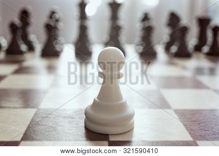 Single pawn against many enemies as a symbol of difficult unequal fight or struggle of minorities. Background in blur. poster
