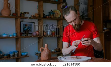Professional male potter shaping and scraping dry clay cup with special tool in pottery workshop, studio. Crafting, artwork and handmade concept poster