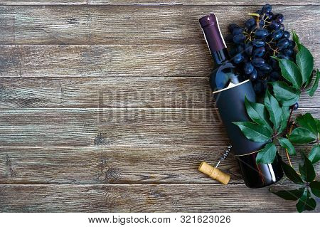 Wineglasses With Red Wine, Bottle, Corkscrew, Blue Grapes, Leaves On A Wooden Table. Wine Background