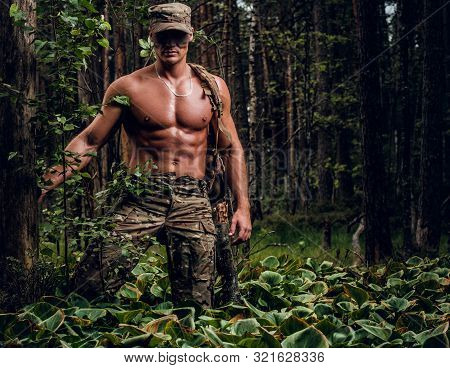 Brutal Muscular Man In Military Uniform And Naked Torso Is Posing For A Photographer In The Forest.