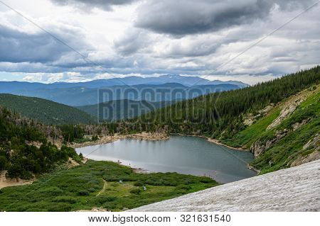 Saint Mary's Lake in Colorado with Rocky Mountains as background on a cloudy day