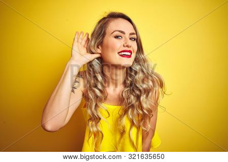 Young attactive woman wearing t-shirt standing over yellow isolated background smiling with hand over ear listening an hearing to rumor or gossip. Deafness concept.