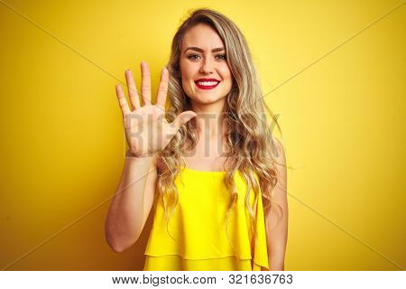 Young attactive woman wearing t-shirt standing over yellow isolated background showing and pointing up with fingers number five while smiling confident and happy.