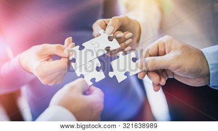 A Group Of Business People Assembling Jigsaw Puzzle. The Concept Of Cooperation, Teamwork, Help And