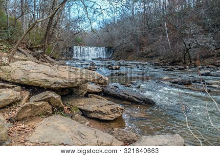 Standing Downstream Looking At The Waterfall Spilling Into The Creek At The Old Mill Park In Roswell