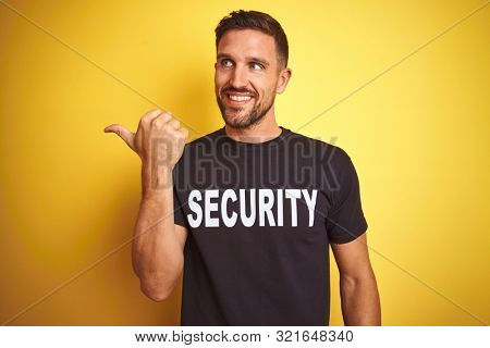 Young safeguard man wearing security uniform over yellow isolated background smiling with happy face looking and pointing to the side with thumb up.