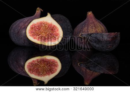 Group Of Three Whole Two Halves Of Meaty Fresh Fig Fruit Isolated On Black Glass