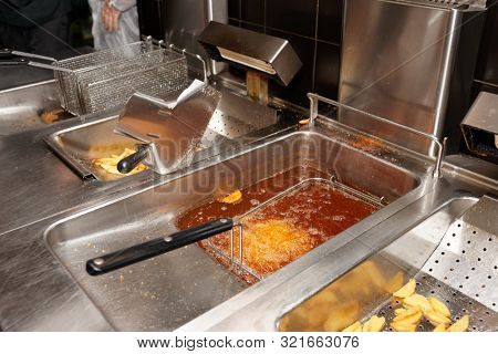 Deep fryer with boiling oil in commercial kitchen, fast food restaurant