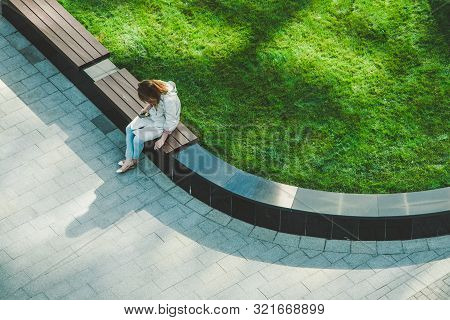 Frustrated Caucasian Woman With The Phone And Cigarette Sitting On The Wooden Bench In The Garden. B