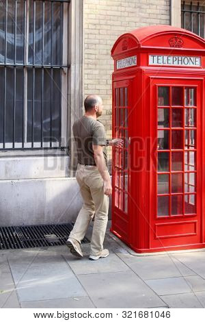 A photography of a old red phone box in London with man