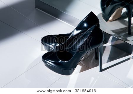poster of Black patent leather high-heeled shoes standing on the floor near the mirror. High heel shoes. A pair of beautiful female high heel shoes.