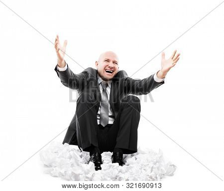 Business problems and failure at work concept - loud shouting or screaming tired stressed businessman gesturing raised hands sitting down floor on crumpled torn paper document heap white isolated
