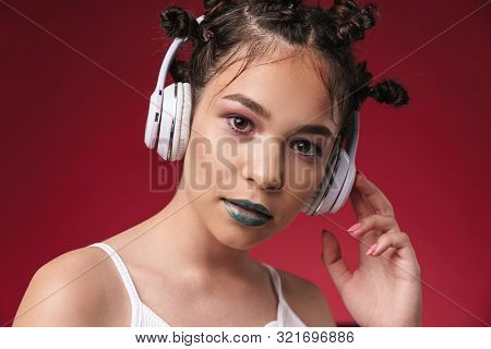 Image closeup of pretty punk girl with bizarre hairstyle and dark lipstick listening to music with headphones isolated over red background poster