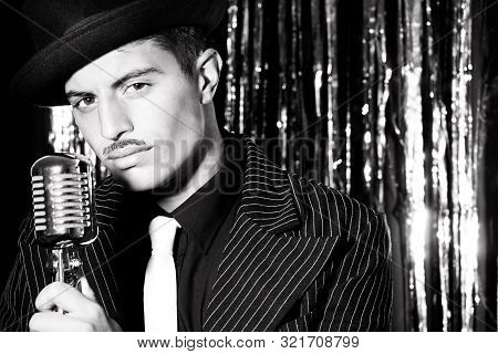 Attractive latino man singing in front of vintage microphone in nightclub with silver curtain in background poster