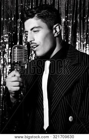 Attractive Latino Man Singing In Front Of Vintage Microphone In Nightclub With Silver Curtain In Bac