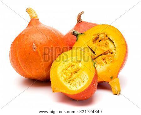 Hokkaido squashes or Red Kuri squashes on white background. Isolated group of whole and halved fruits