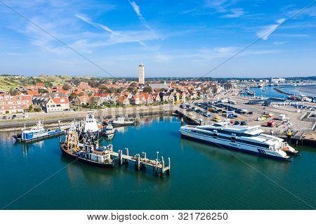 Netherlands, Terschelling - Aug 25, 2019: Brandaris Lighthouse Towers Up. Catamaran Ms Tiger Moored