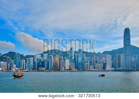 HONG KONG, CHINA - MAY 1, 2018: Hong Kong skyline cityscape downtown skyscrapers over Victoria Harbour with tourist junk boat on sunset. Hong Kong, China