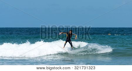 Sables D Or Les Pins, Bretagne / France - 20 August 2019: A Young Athletic Man Catching A Wave And S