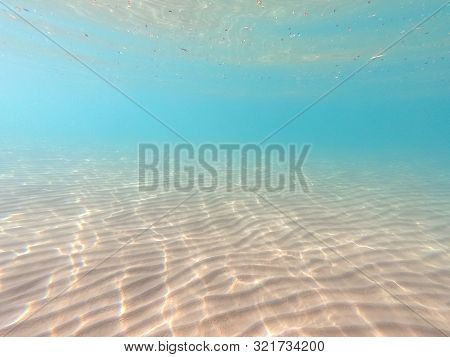 Clear Water. Underwater Background With Sandy Sea Bottom. Beautiful Texture Of The Sea And Ocean Wat