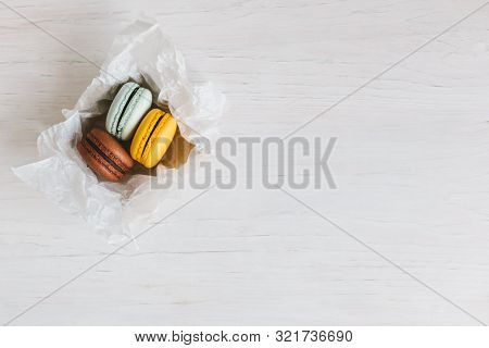 Three French Macarons In Gift Box On A White Wooden Table. Chocolate, Yellow And Light Blue Macarons