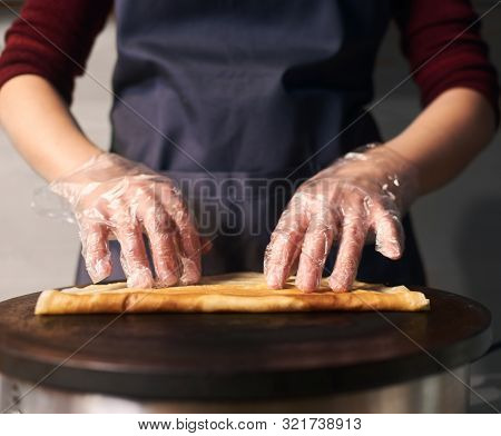 Cropped View Of Professional Cook In Apron While Baking Crepe Process On Hot Round Cooktop. Skillful