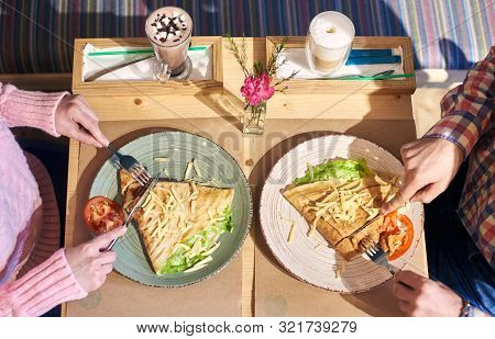 Cropped Hands Of Man And Woman Savoring Food Omelet And Coffee For Lunch Sitting At Wooden Table In