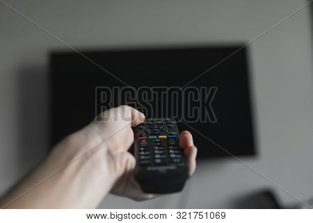 poster of The man with the remote control in hand want switch on the TV and presses the button on the remote control. Remote control in hand closeup.