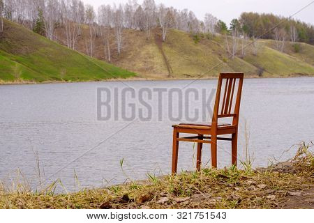 Wooden Chair On The River Bank Near The Water Is Empty It Is Unoccupied. Chair For Relaxation And En