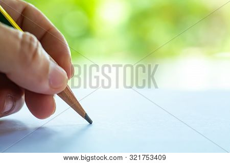 Woman's Left Hand Holding Multicoloured Pencil (yellow & Green Colour), Writing Letter On White Pape