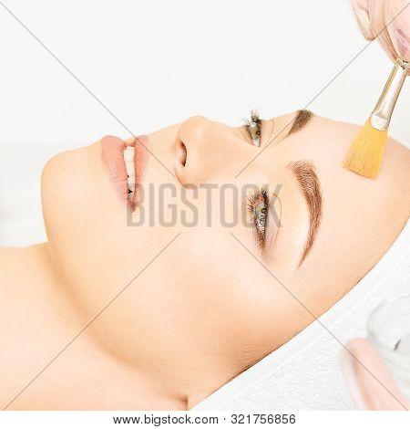 Facial Brush Peel Retinol Treatment. Beauty Woman Peeling Procedure. Cosmetology Young Girl Therapy.