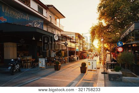 Stavros, Greece - August 29, 2019: The Main Street Of The Town Full Of Shops And Restaurants During