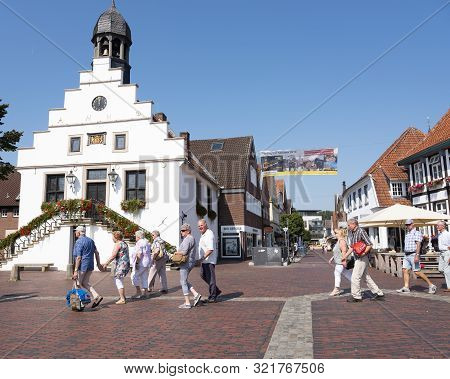 Lingen, Germany, 27 August 2019: Senior Tourists Pass Old Town Hall On Market Square In German Town