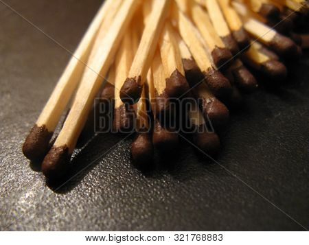 A Group Of Matches Are Scattered On A Black Leather Surface. Ordinary Brown-headed Matches Wallow In
