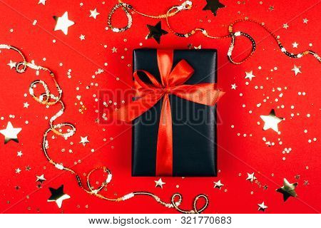 Gift Box On Trendy Red Background With Sparkles. Flat Lay Style