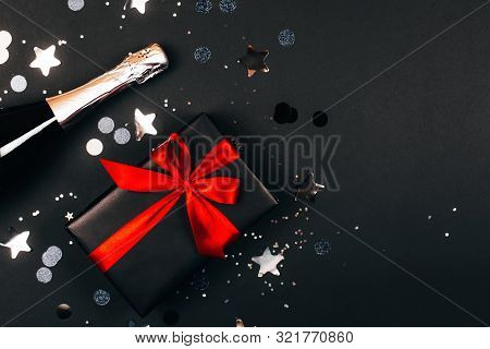 Champagne With Gift Box On Black Background. Flat Lay Style