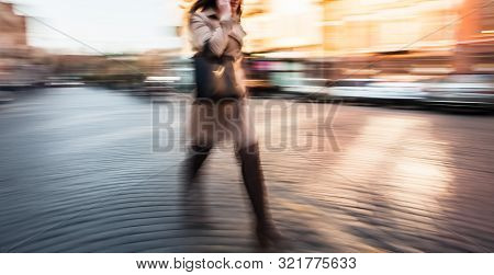Abstract Image Of A Young Woman Talking On A Cell Phone In A Hurry. Intentional Motion Blur