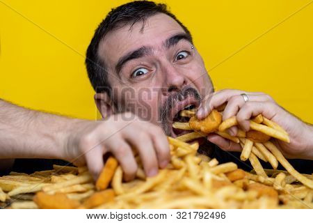 Eating Junk Food Nutrition And Dietary Health Problem Concept. Young Man Eating With Two Hands A Hug