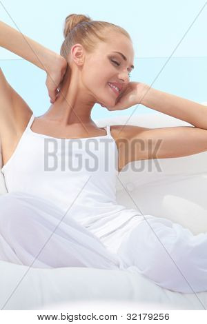 Pretty woman in casual outfit curled up on a white window seat stretching languidly in the warm sunshine