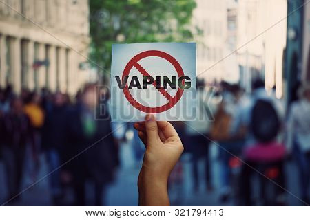 Human Hand Holding A Protest Banner Stop Vaping Message Over A Crowded Street Background. Banning Fl