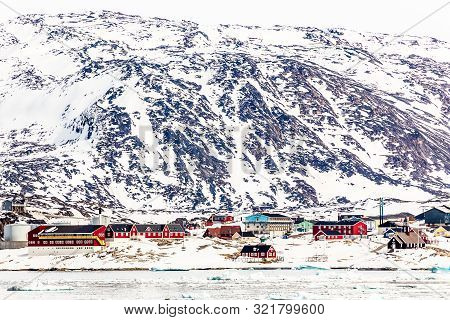 Arctic City Panorama With Colorful Inuit Cottages And Oil Factory On The Rocky Hills Covered In Snow