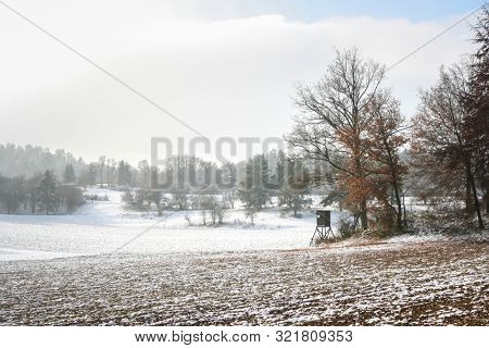 A photography of a snowscape with hunter stand