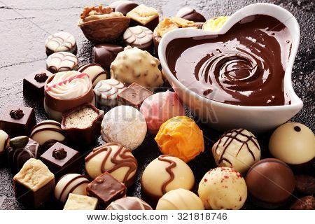 A Lot Of Variety Chocolate Pralines, Belgian Confectionery Gourmet Chocolate On Rustic Dark Backgrou