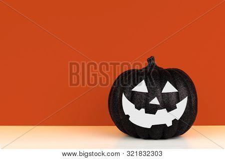 Black Halloween Jack O Lantern Decoration On A Wood Shelf Against An Autumn Orange Background