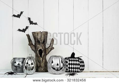 Rustic Halloween Display With Jack O Lantern Decor And Spooky Tree Against A White Wood Background W