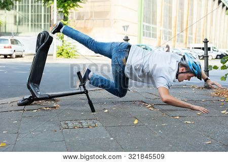 Man Having Accident Falling From E-scooter On Street
