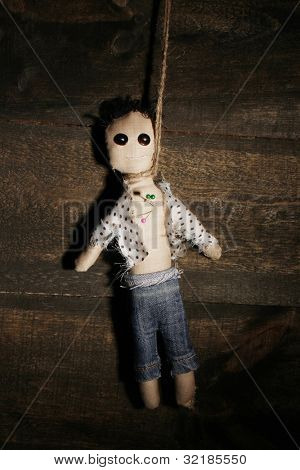 Hanged doll voodoo boy on wooden background