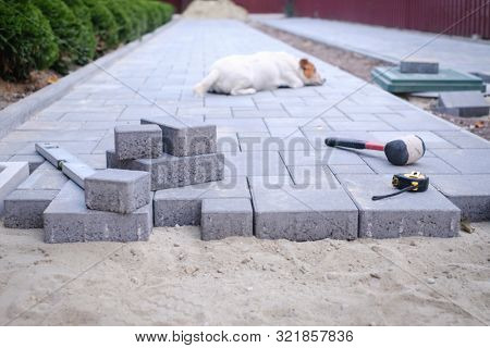 Paving stones pathway paving background. Installing tools on foreground
